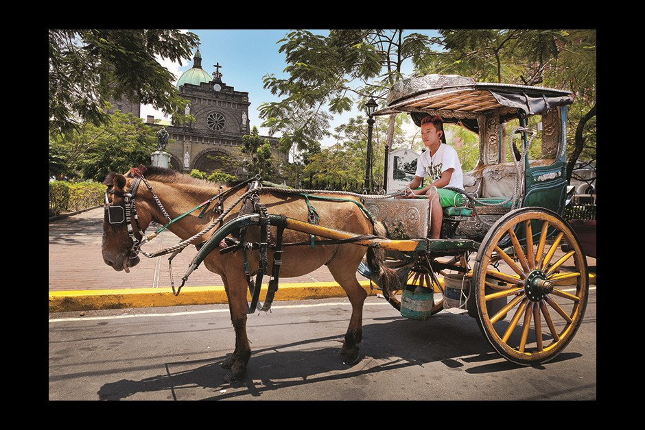 HORSE-DRAWN CARRIAGES OUTSIDE MANILA CATHEDRAL OFFER TOURS OF INTRAMUROS