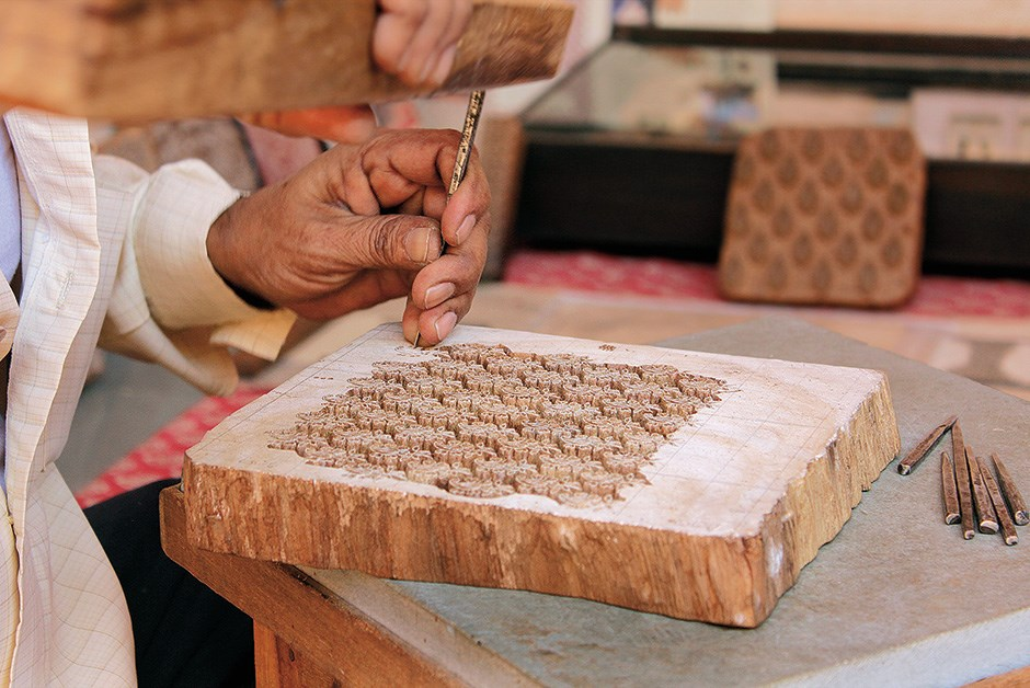 Block cutter Mujeeb Khan freehands a complex pattern in teak; Anokhi applies the traditional prints to modern goods, such as these patterned notebooks