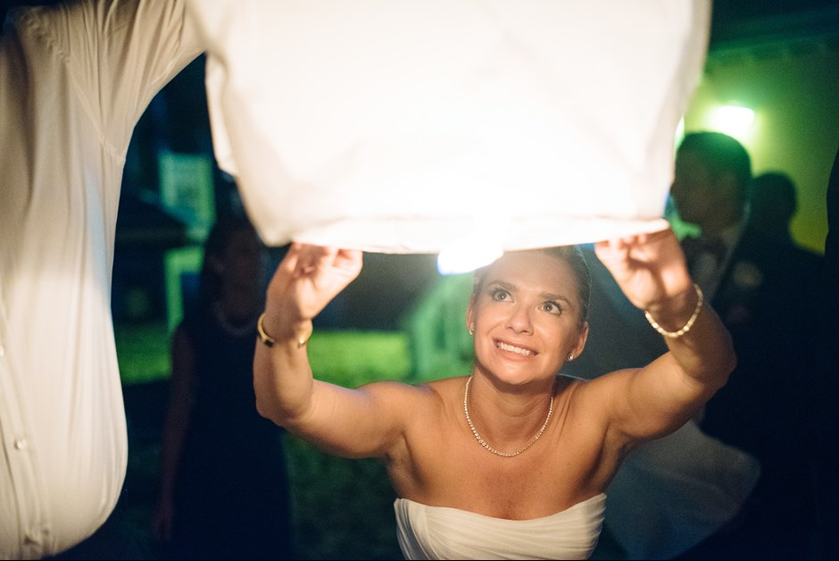 Bride lighting lantern on the beach at Fairmont