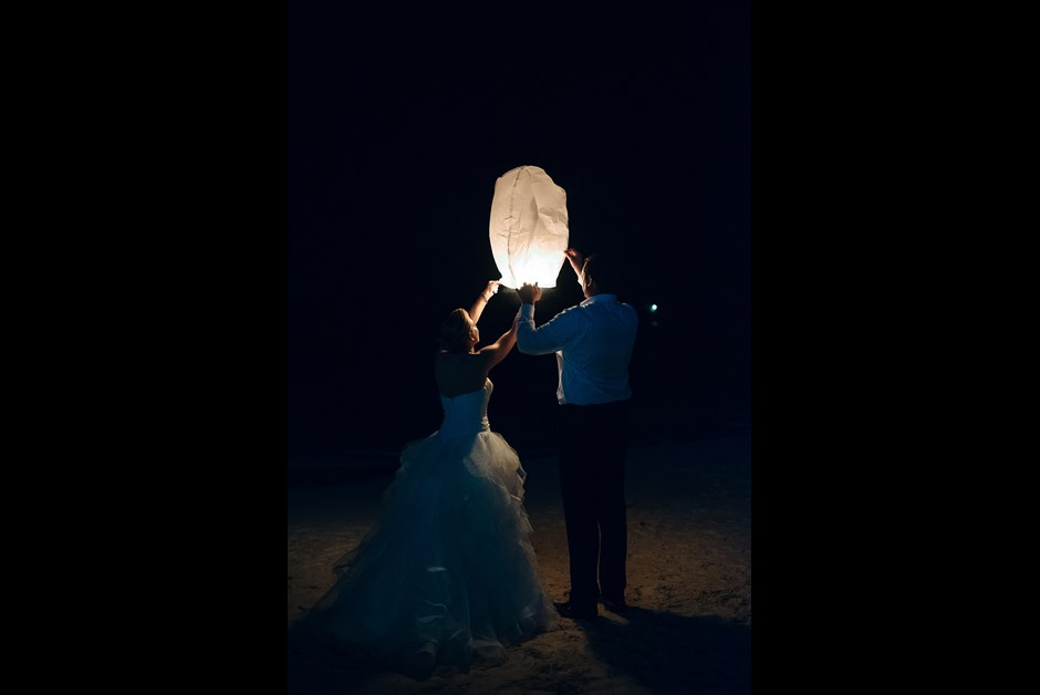 Bride and Groom light lantern on Fairmont Beach